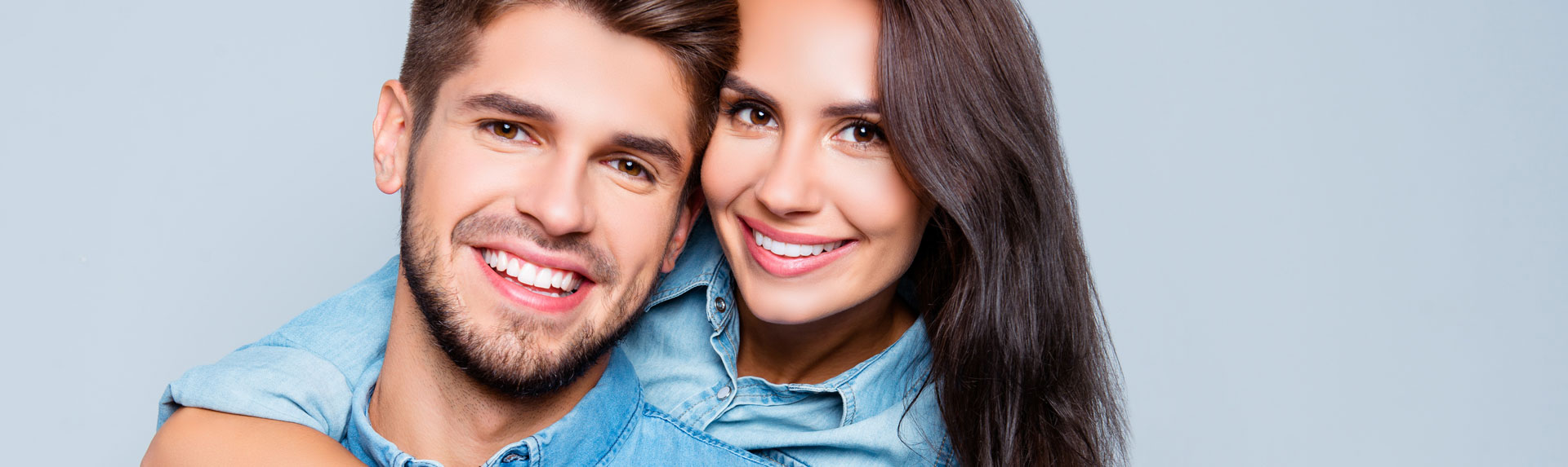 Smiling young couple at blue background